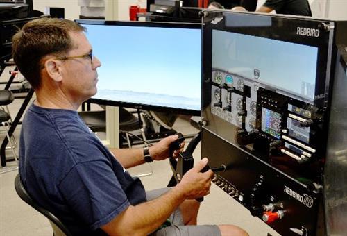 A Fontana Unified administrator pilots a Cessna 172 in a Redbird flight simulator at A.B. Miller High School during the Distr